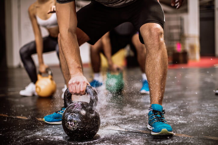 Athletes who take part in activities that involve explosive movements, like these people working out with kettlebells, might need a higher daily carb intake than others.